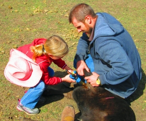 Raelyn and John vaccinating the calf
