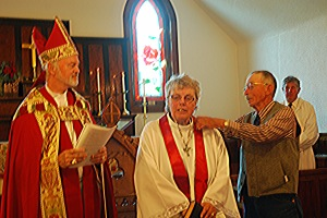 Bishop Smylie looks on as Reverend Fleming is robed by her husband , John.
